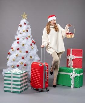 Garota loira com chapéu de papai noel olhando para a cesta de presentes
