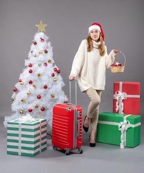 Garota loira com chapéu de papai noel segurando uma cesta com brinquedos vermelhos de natal