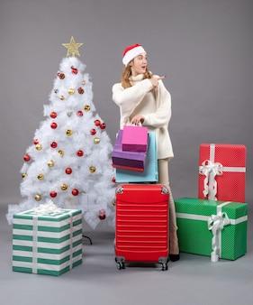 Garota loira com chapéu de papai noel segurando uma valise vermelha de frente