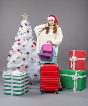 Garota loira com chapéu de papai noel segurando uma valise vermelha e sacolas de compras mostrando a placa de liga para mim