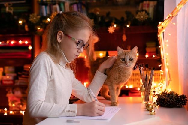 Garota loira criança com grandes óculos cor de rosa e pretos, escrevendo a carta para o papai noel