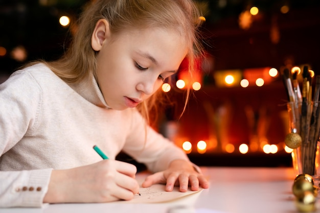 Garota loira criança escrevendo a carta para o papai noel ou algo de desenho na com bokeh amarelo quente
