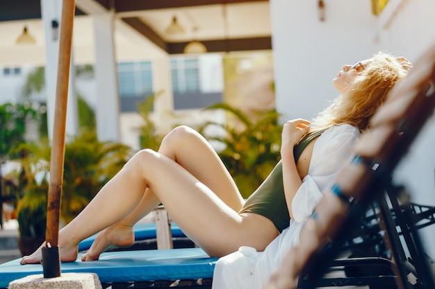 Garota loira de bronzeamento e relaxar na piscina