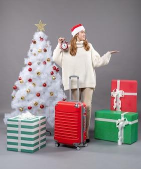 Garota loira de natal com uma valise vermelha segurando um despertador vermelho de frente