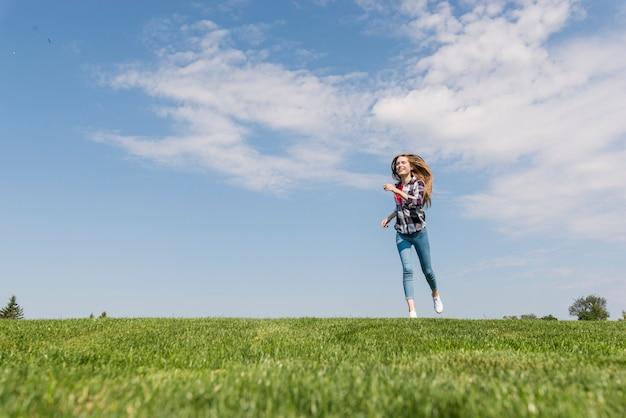 Garota loira de vista frontal correndo na grama