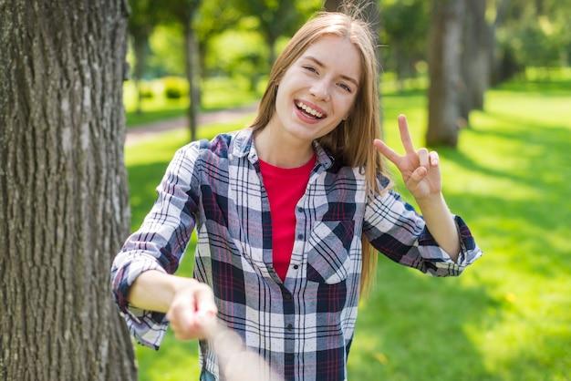 Garota loira de vista frontal tomando um selfie ao lado de uma árvore