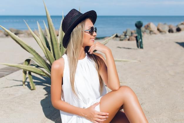 Garota loira e bonita com cabelo comprido está sentada na praia perto de cacto no fundo. ela está olhando para longe.