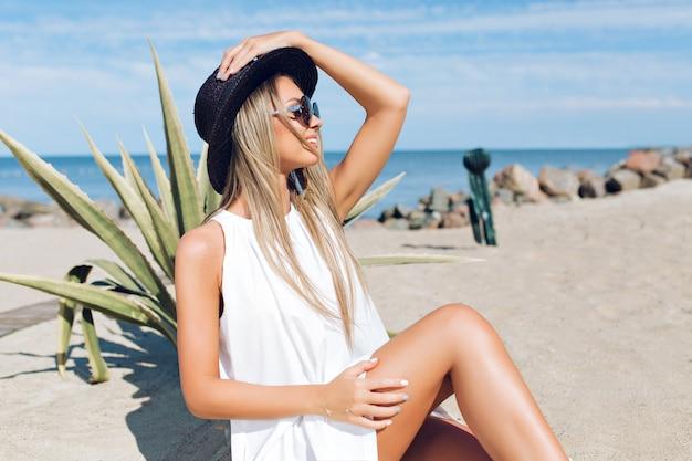 Garota loira e bonita com cabelo comprido está sentada na praia perto de cacto no fundo. ela está segurando um chapéu e olhando para longe.