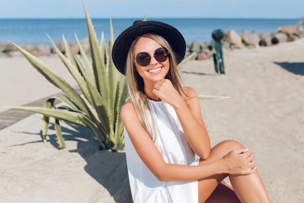 Garota loira e bonita com cabelo comprido está sentada na praia perto de cacto no fundo. ela está sorrindo para a câmera.