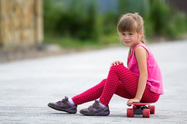 Garota loira e bonita em roupas cor de rosa, sentado no skate