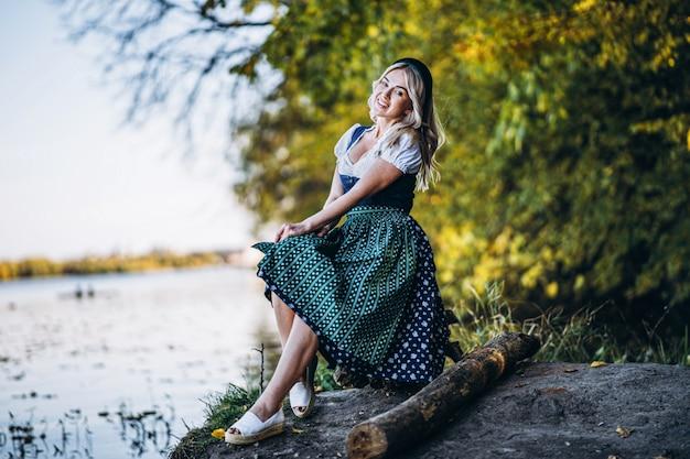 Garota loira e bonita feliz em vestidos casuais, festival de cerveja tradicional, sentado ao ar livre com árvores coloridas blured atrás