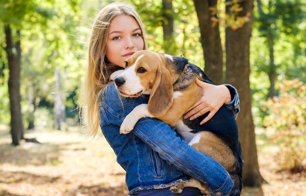 Garota loira e bonita, segurando o cachorro beagle