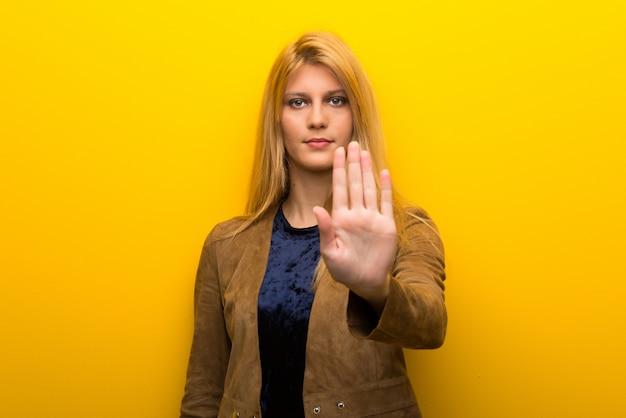 Garota loira em fundo amarelo vibrante, fazendo o gesto de parada, negando uma situação que pensa errado