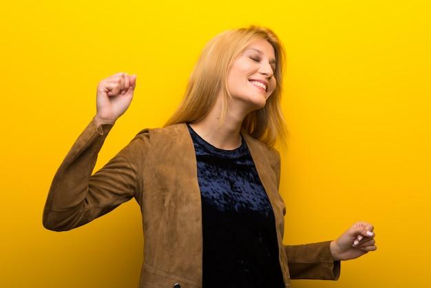 Garota loira em fundo amarelo vibrante gosta de dançar enquanto ouve música em uma festa