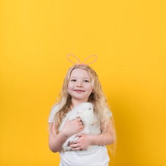 Garota loira em orelhas de coelho com coelho cute