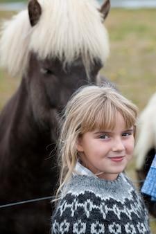 Garota loira em pé na frente de um cavalo islandês