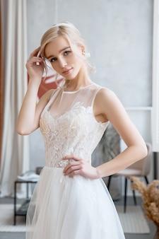 Garota loira em um lindo vestido de noiva branco. noiva mulher está esperando o noivo antes do casamento