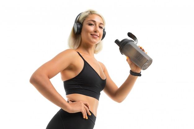 Garota loira em um uniforme de esportes segura uma garrafa de água e ouve música