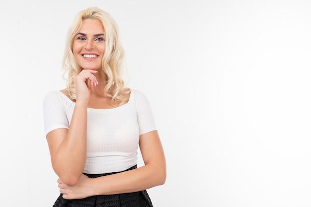 Garota loira em uma camiseta branca, posando em um fundo branco, com espaço de cópia