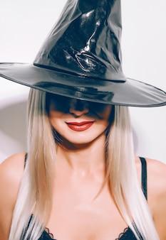 Garota loira em uma fantasia de bruxa de halloween em uma superfície branca