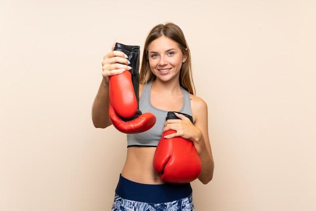Garota loira esporte jovem sobre fundo isolado com luvas de boxe