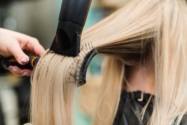 Garota loira fazendo o cabelo dela