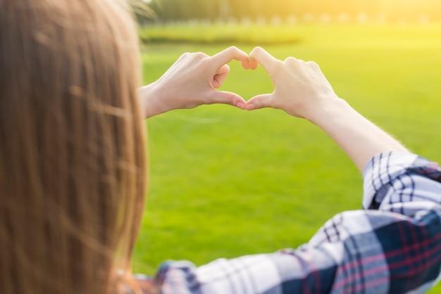 Garota loira fazendo um coração com as mãos