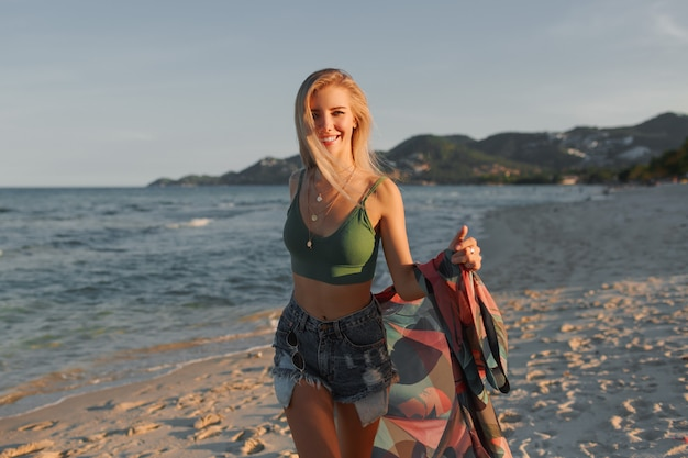 Garota loira feliz correndo na praia, aproveitando o verão.