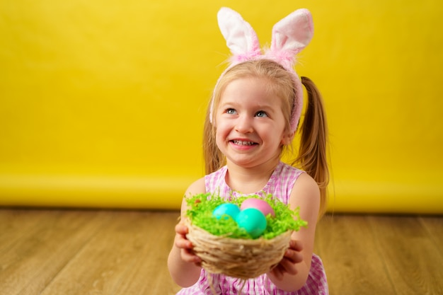 Garota loira feliz da criança com orelhas de coelho e cesta de ovos para a páscoa