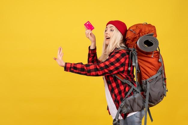 Garota loira feliz de frente com sua mochila segurando um cartão