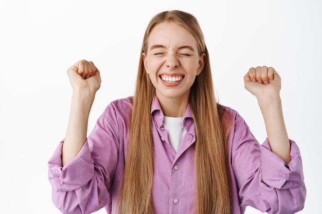 Garota loira feliz e bem-sucedida se regozijando, diga sim, balançando o punho e comemorando a vitória, torne-se vencedora, alcance a meta, triunfando em pé contra a parede branca