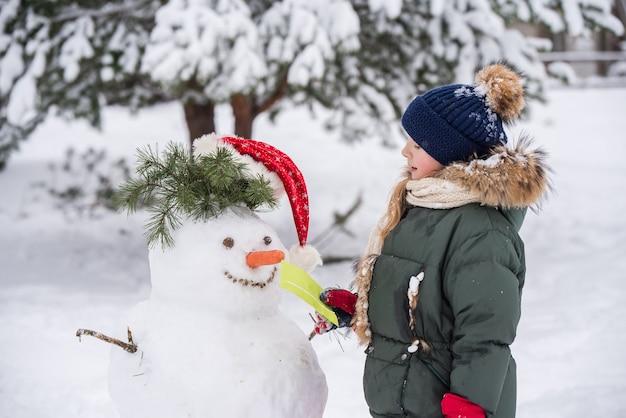 Garota loira feliz e linda criança dando uma carta para um boneco de neve