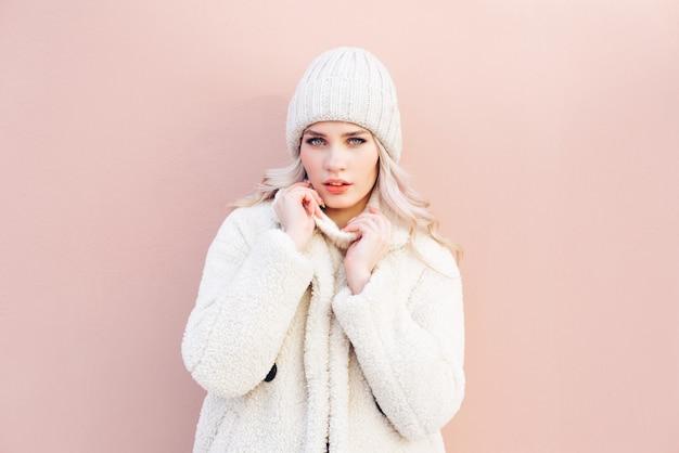 Garota loira feliz em roupas de inverno branco posando contra uma parede rosa.
