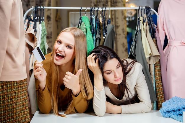 Garota loira feliz fazendo compras com um cartão de crédito