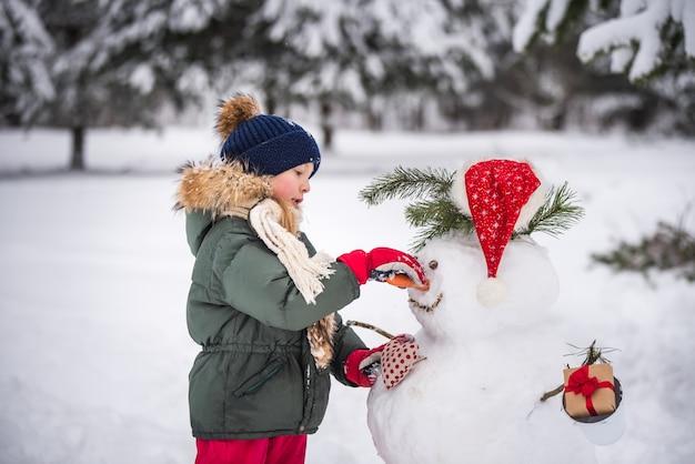 Garota loira feliz linda criança brincando com um boneco de neve em uma caminhada de inverno com neve