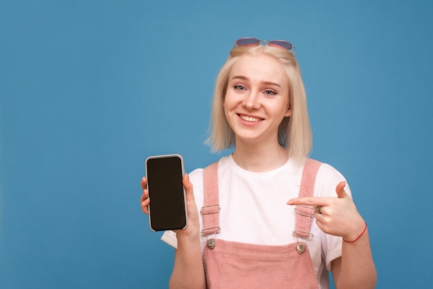 Garota loira feliz mantém um smartphone com uma tela preta, mostra um dedo na tela