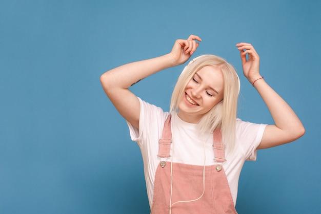 Garota loira feliz ouve música em fones de ouvido com os olhos fechados, sobre um fundo azul, dançando e sorrindo