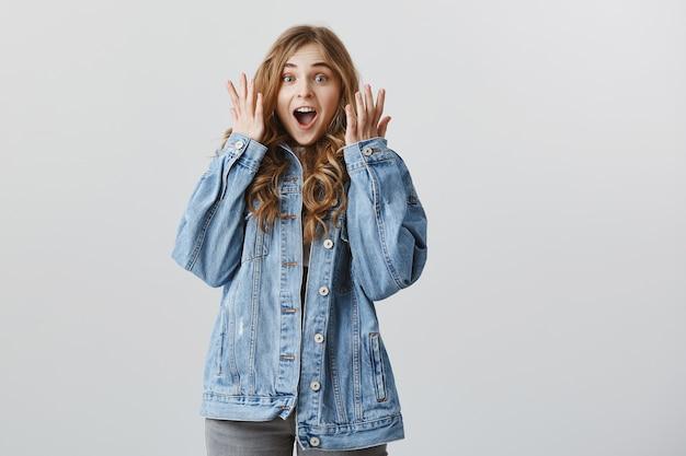 Garota loira feliz surpresa reage a uma notícia maravilhosa, grito de alegria