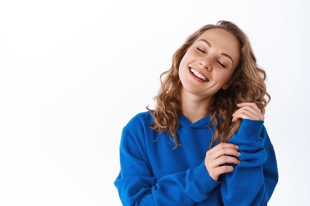 Garota loira feliz tocando seu cabelo cacheado macio com um sorriso satisfeito e olhos fechados, aproveite a suavidade após o shampoo, em pé sobre uma parede branca