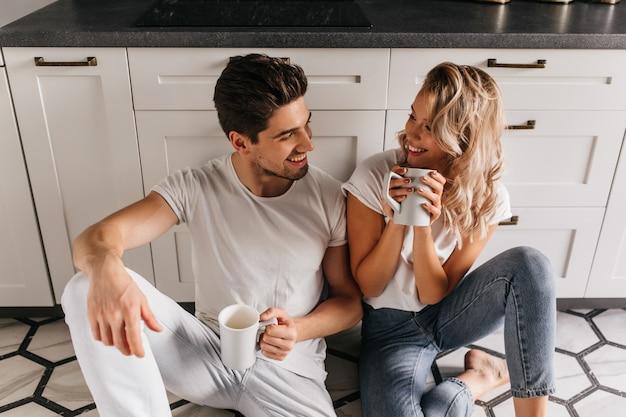 Garota loira incrível, passando a manhã com o namorado. mulher caucasiana atraente, bebendo café com o marido.
