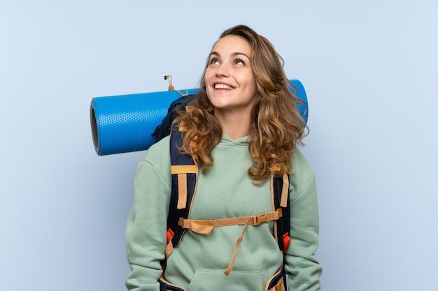 Garota loira jovem alpinista sobre parede azul isolada, olhando para cima enquanto sorrindo