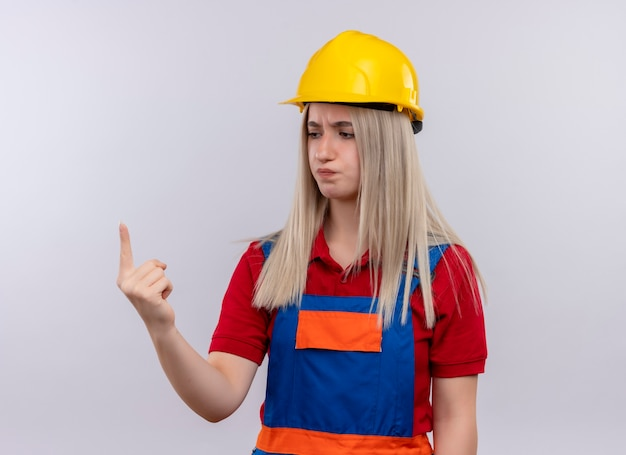 Garota loira jovem construtora insatisfeita de uniforme, mostrando um com a mão e olhando para ela na parede branca isolada