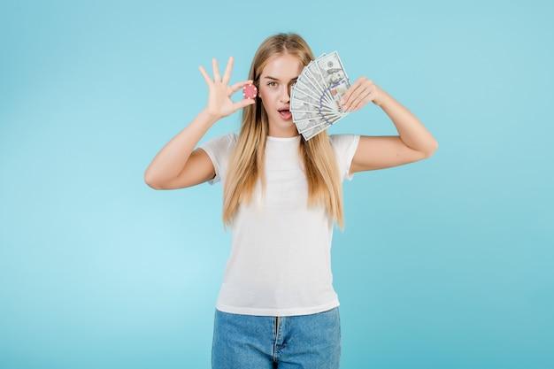 Garota loira jovem e atraente com ficha de poker do casino online e dinheiro isolado sobre o azul