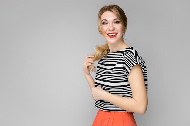 Garota loira jovem e atraente na blusa listrada, sorrindo, segurando o cabelo em pé na parede cinza