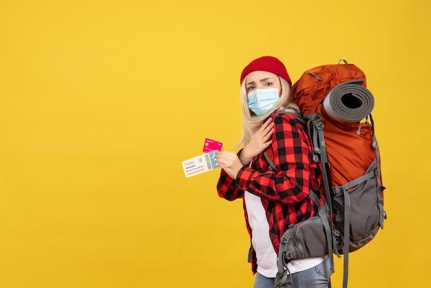 Garota loira legal com sua mochila segurando o cartão e a passagem