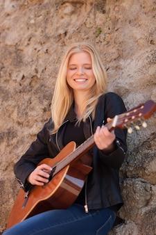 Garota loira legal tocando guitarra ao ar livre
