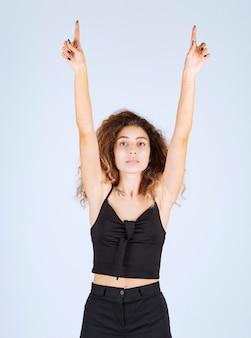 Garota loira levantando a mão e apontando algo acima com emoções.