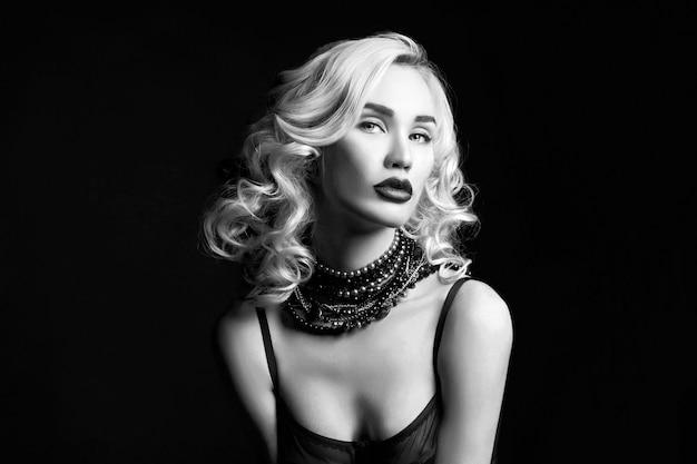 Garota loira linda sexy com cabelo comprido. retrato de mulher perfeita em fundo preto. cabelo lindo e olhos bonitos