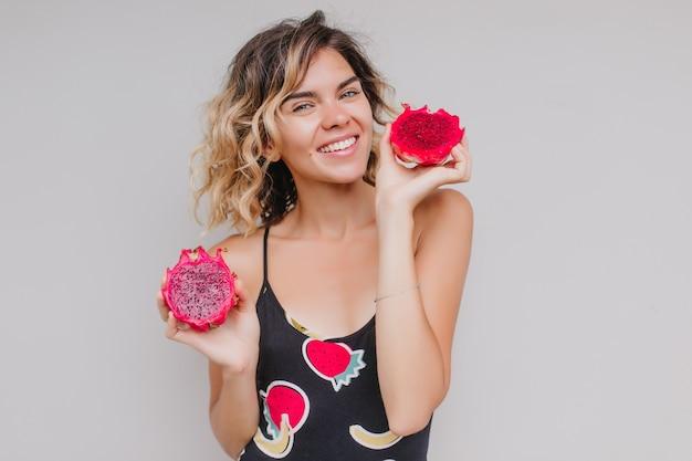 Garota loira na moda posando com frutas exóticas. tiro interno de entusiasmada senhora caucasiana em vestido segurando pitaya.