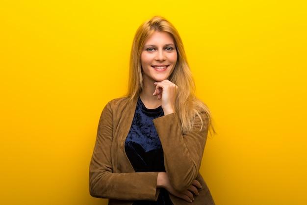 Garota loira no fundo amarelo vibrante sorrindo e olhando para a frente com cara confiante